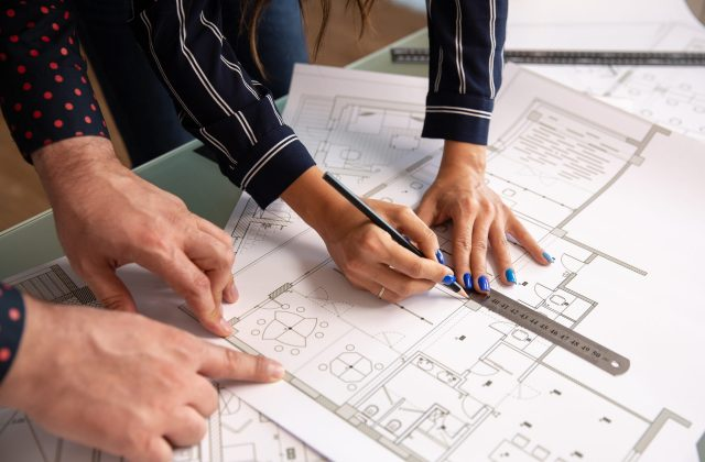 Close up with the hands of two architects sketching something in a house plan. blueprints and team work